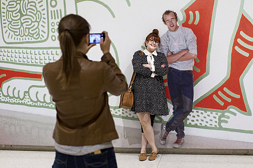 A visitor poses with a photo of Keith Haring during Walktoberfest