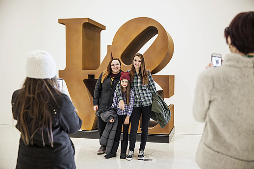 Visitors with Robert Indiana's LOVE (1966/1998) in the exhibition 75 Gifts for 75 Years, 2015